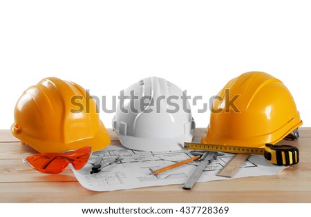 Construction drawings with tools on wooden table isolated on white background