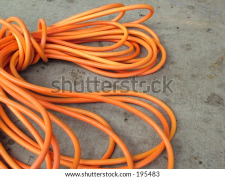 Construction electrical cord on stained cement - stock photo