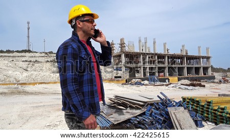 Construction Engineer.Construction engineer (worker) talking on the phone and looking to tablet pc. - stock photo