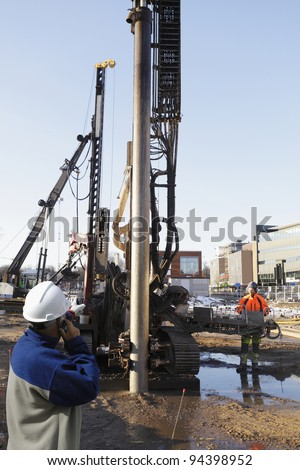 construction engineer directing giant excavator inside building-site, cranes and machinery - stock photo
