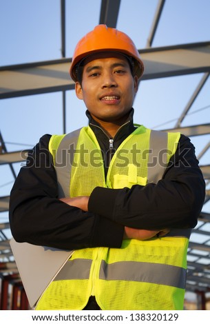 construction engineer holding a notepad with safety vest  looking at the camera - stock photo