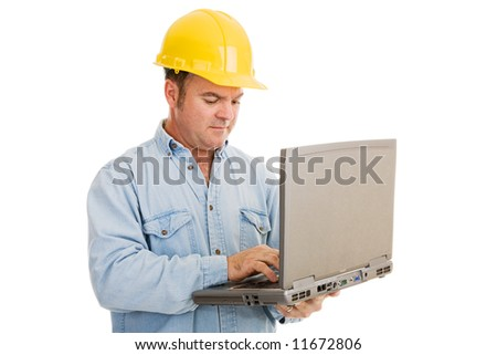 Construction engineer using his laptop computer on the job.  Isolated on white. - stock photo