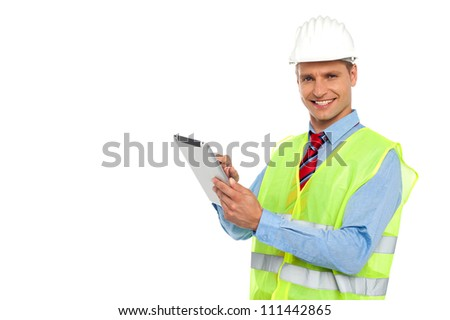 Construction engineer wearing safety hat and operating wireless device - stock photo