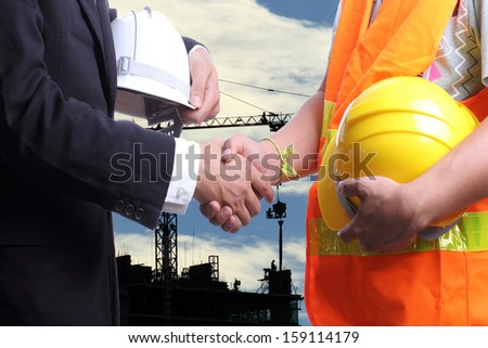 Construction engineer with crane and building site - stock photo