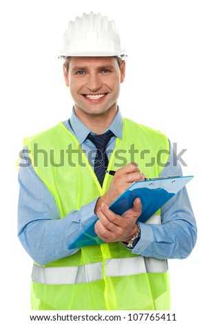 Construction engineer with safety hat writing on notepad against white background