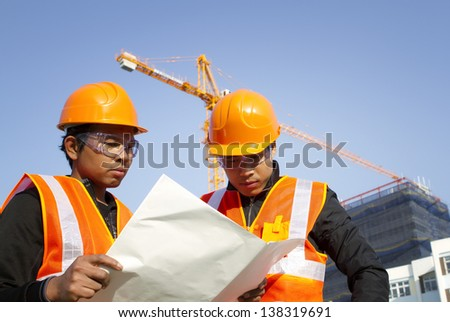 construction engineer with safety vest discussion under construction - stock photo