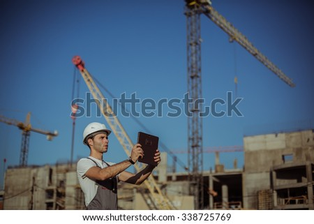 Construction engineer with the tablet pictures of objects on a construction site