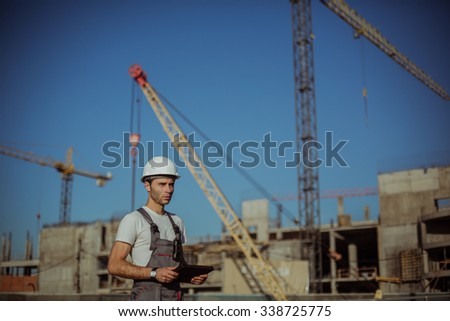 Construction engineer with the tablet pictures of objects on a construction site - stock photo