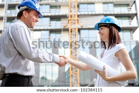 Construction engineers shaking hands at the construction site. Selective focus. - stock photo