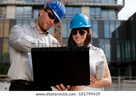 Construction engineers / specialists planning at a construction site - stock photo
