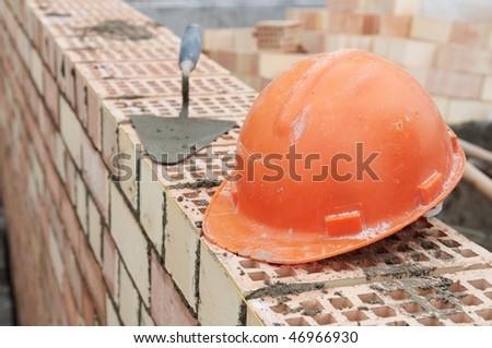 Construction equipment for brick building work helmet trowel and pecker - stock photo