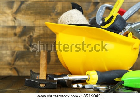 Construction equipment on wooden background - stock photo
