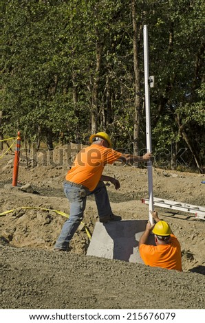 Construction excavation contractor uses a level rod and laser to install a concrete sewer vault structure - stock photo