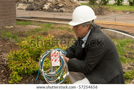 construction foreman attaching a lockout tag to electrical wires - stock photo