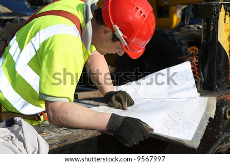 Construction foreman checking drawings - stock photo