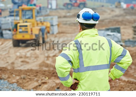 construction foreman worker is watching building works on site  - stock photo