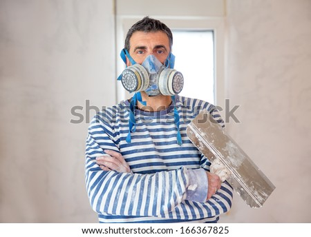 construction funny plastering man mason with protective mask and trowel in hands - stock photo