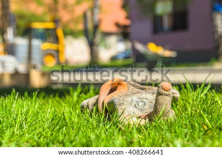 Construction glove on the green grass show the middle finger with empty construction site in background.Concept of worker revolt - stock photo