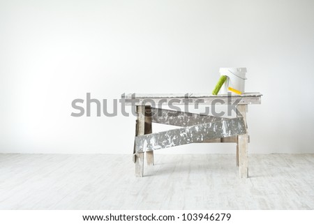 Construction grunge ladder, paint roller and paint bucket in white interior: white wall and gray floor. Apartment decoration concept. - stock photo