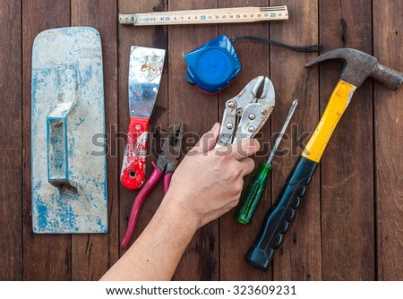 Construction hand tools with hand over wooden floor - stock photo