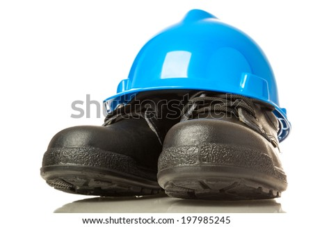 Construction hardhat and work boots on white background - stock photo