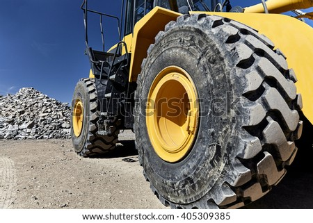 Construction heavy equipment loader and bucket on jobsite with gravel and rocks - stock photo