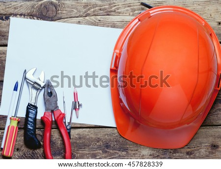 construction helmet, old tools and a blank paper sheet lying on a wooden surface.view from above.toned
