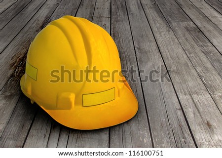 Construction helmet on wooden background - stock photo