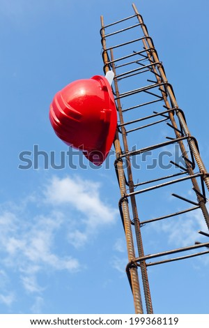 Construction industry still life with helmet hanging on steel bars - stock photo