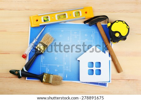 Construction instruments, plan and brushes on wooden table background - stock photo
