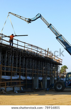 Construction job site: Lifting lumber to building roof with crane - stock photo