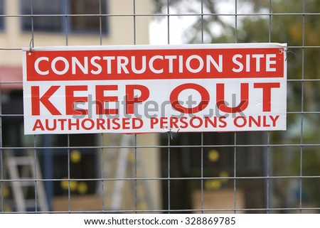 Construction keep out sign on a fence with a building site behind it. - stock photo