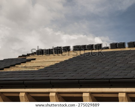 construction, laying ceramic tile roof on wooden house - stock photo