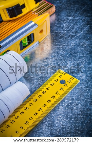Construction level blueprints and units of measurement on metallic scratched background building and architecture concept. - stock photo