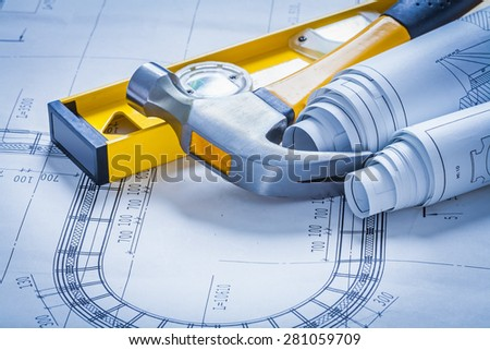 Construction level claw hammer and set of blueprints maintenance concept  - stock photo