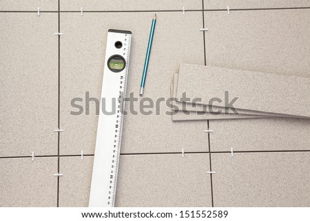 Construction level with pencil on tile floor