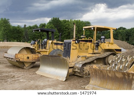Construction Machinery - dozers, earthmovers, etc. on construction site - stormy sky - stock photo