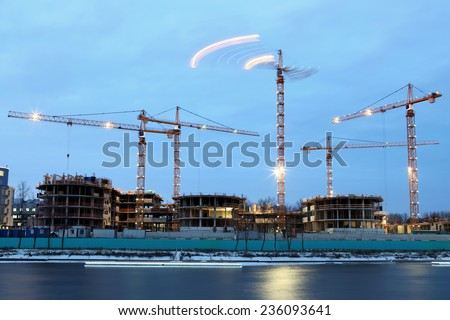 Construction machinery on the construction of residential buildings, night time Evening illumination, lifting equipment, tower cranes with night lights.