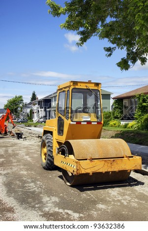 Construction, making pavement on small town street with used yellow asphalt roller on dirt and gravel at the job site with mechanical digger and concrete sidewalk - stock photo