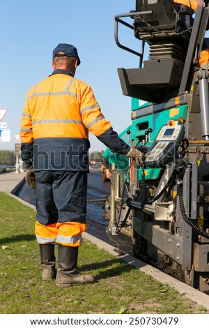 Construction man worker operating tracked paver machine during road asphalting works - stock photo