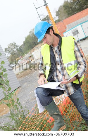 Construction manager using electronic tablet on site - stock photo