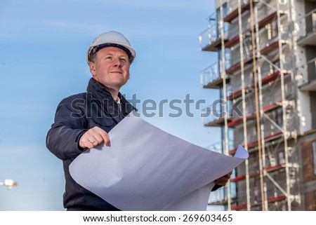 Construction manager with blueprints standing in front of construction site.