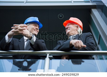 Construction managers in helmets talking out of the building