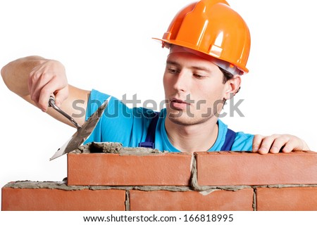 Construction mason installing red brick with trowel - stock photo