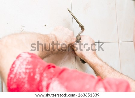 construction mason man hands on tiles work with cement mortar - stock photo