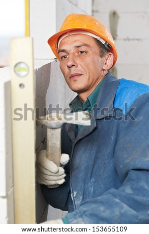construction mason worker bricklayer inspecting with level installation of calcium silicate brick during indoor wall creation