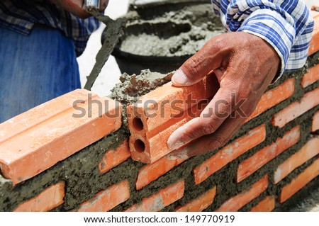construction mason worker bricklayer installing brick  - stock photo