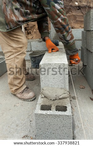 Construction mason worker bricklayer  laying concrete block foundation wall with spatula outdoors - stock photo