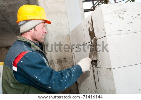 construction mason worker bricklayer making a brickwork with trowel - stock photo