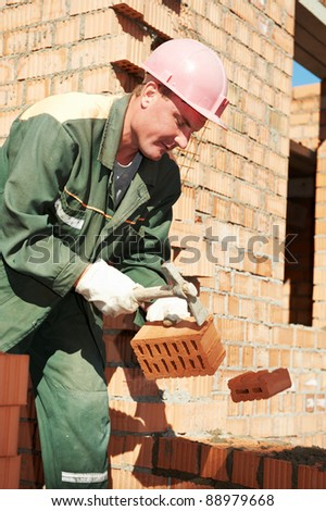 construction mason worker bricklayer making a brickwork with trowel and cement mortar